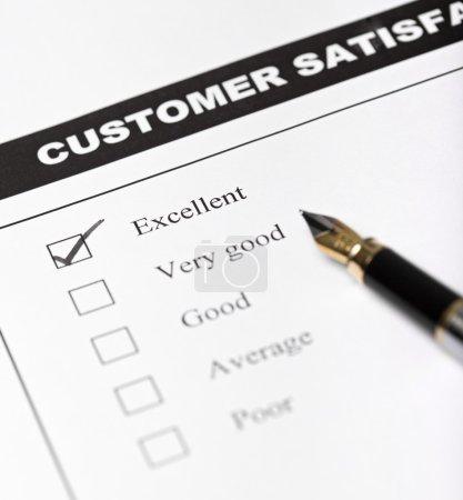 Customer satisfaction survey form with pen - closeup