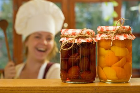 Happy woman chef with homemade canned fruit