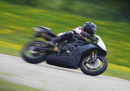 A motorcycle racers speed past in a blur....