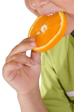 Photo pour Gros plan d'un garçon mangeant une tranche d'orange - isolé - image libre de droit