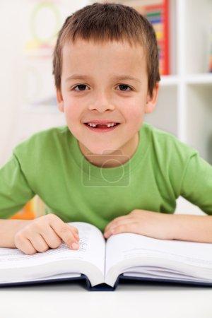 Happy elementary school boy practice reading