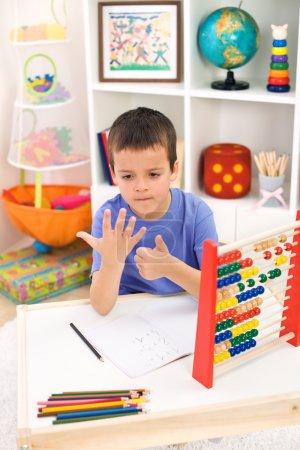Photo pour Petit garçon prépare pour l'école primaire, faire des exercices de mathématiques simples - image libre de droit