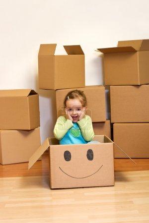 Photo pour Petite fille dans une boîte en carton avec un sourire - concept émouvant - image libre de droit