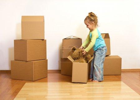 aufgeregtes kleines Mädchen beim Auspacken in ihrem neuen Zuhause