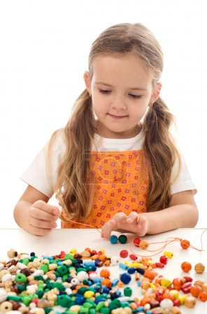 Photo for Little girl playing with beads and a string at the table - isolated - Royalty Free Image