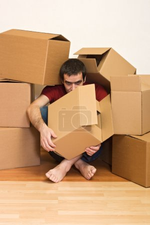Photo for Man under lots of cardboard boxes on the floor - moving concept - Royalty Free Image