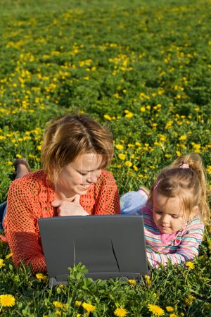 Woman and little girl on the spring flower field