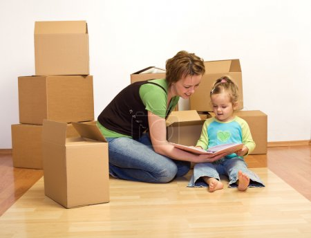 Photo for Unpacking in our new home - woman and little girl with cardboard boxes sitting on the floor - Royalty Free Image