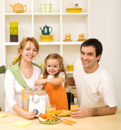 Photo pour Faire du jus de fruits est tellement amusant - petite fille dans la cuisine avec ses parents - image libre de droit