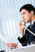 Successful businessman with phone and document at office