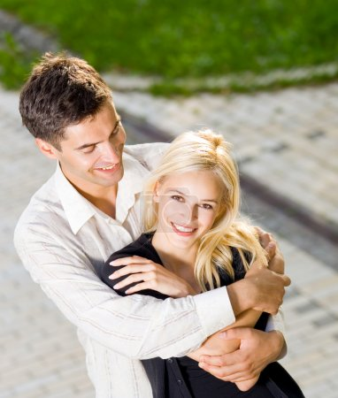 Photo for Young happy amorous embracing couple, outdoors - Royalty Free Image