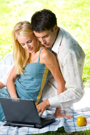 Young happy smiling couple with laptop at picnic