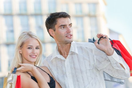 Young attractive happy amorous couple with shopping bags outdoor