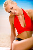 Young sexy smiling happy woman in sportwear sitting on the beach
