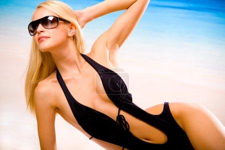 Photo pour Jeune belle sexy bronzée heureuse femme en maillot portant pendant le bain de soleil sur la plage de la mer et des lunettes de soleil - image libre de droit