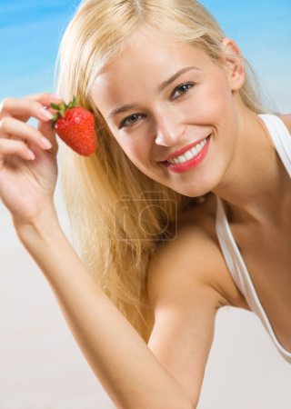 Young happy smiling woman with strawberry on beach