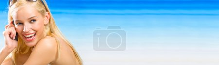 Young beautiful blond woman with cellphone on the beach. To prov