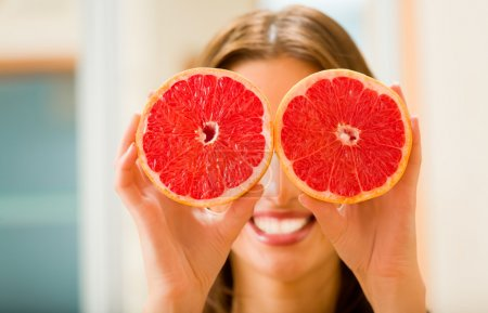 Photo for Young woman with grapefruit at home - Royalty Free Image