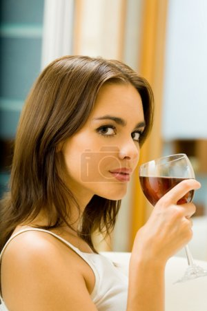 Young woman with glass of red wine, indoors