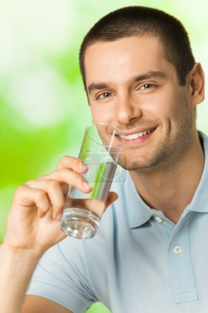 Young happy smiling man drinking water, outdoors