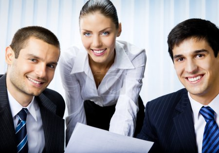 Three businesspeople working with document at office