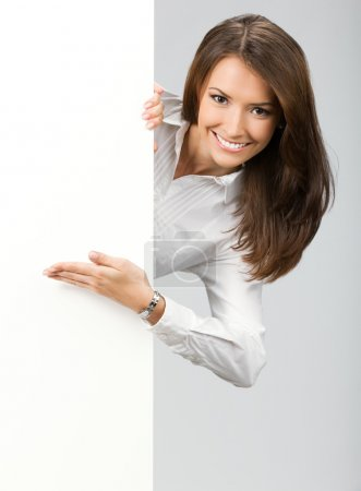 Photo for Happy smiling young business woman showing blank signboard, over grey background - Royalty Free Image