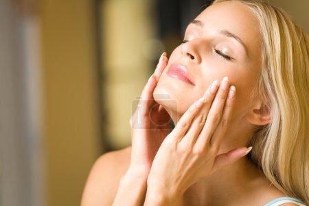 Photo pour Portrait de jeune femme heureuse appliquant de la crème faciale - image libre de droit
