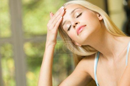 Photo pour Femme avec maux de tête ou d'appliquer la crème sur le visage à la maison - image libre de droit