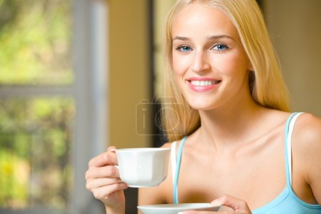 Young beautiful smiling woman with cup of coffee or tea
