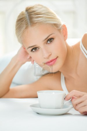 Happy woman with cup of coffee or tea at bedroom