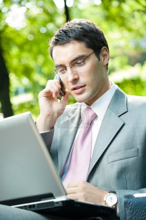 Business man working with laptop and cellphone, outdoors