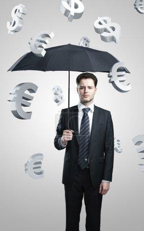 Photo pour Un homme d'affaires avec parapluie sous evro et dollar signe pluie . - image libre de droit