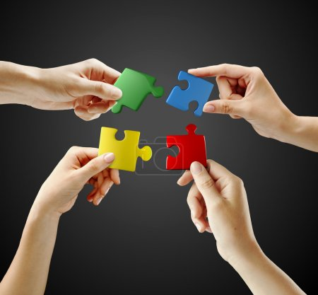 Photo for Hands and puzzle on black background. Teamwork solving a puzzle - Royalty Free Image