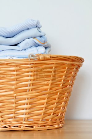 Photo for Baby laundry in a wicker basket - Royalty Free Image