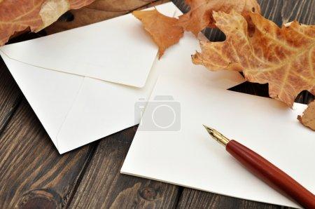 Photo pour Stylo-plume sur lettre vide avec les feuilles de l'automne sur une table en bois - image libre de droit