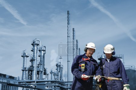 Photo for Two oil-workers, engineers, with refinery industry in background - Royalty Free Image
