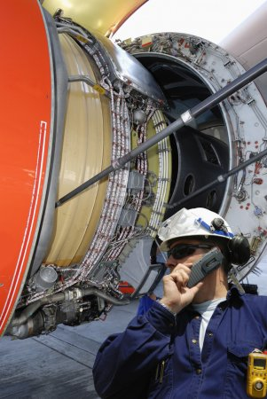 Photo pour Mécanicien d'avion parlant au téléphone avec un grand moteur à réaction en arrière-plan - image libre de droit