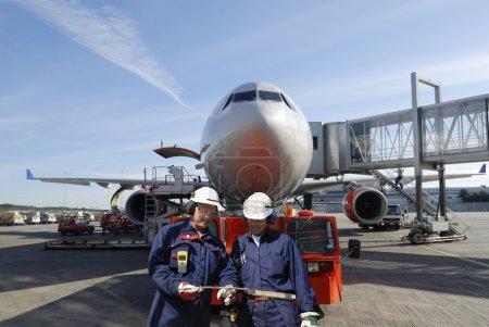 Photo pour Deux mécaniciens de l'air avec grand avion de ligne en arrière-plan - image libre de droit