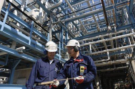 Photo pour Ingénieurs, les travailleurs du pétrole, à l'intérieur de pétrole géant et raffinerie de gaz, pipeline construction derrière les travailleurs - image libre de droit