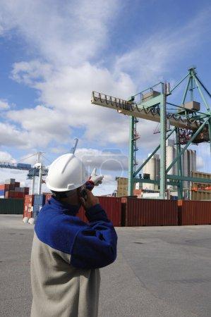 Dock worker directing container crane