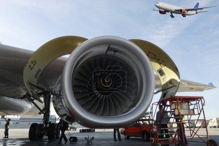 Photo pour Grand réacteur en cours d'entretien au sol, un autre avion arrive pour l'atterrissage - image libre de droit