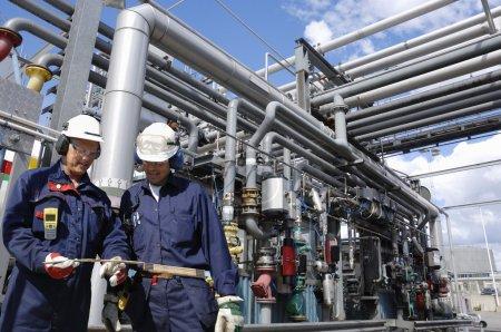 Photo pour Deux ouvriers, ingénieurs, avec de grands oléoducs et oléoducs, vus à l'intérieur de la raffinerie - image libre de droit