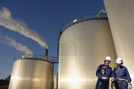 Photo pour Travailleurs, ingénieurs devant des tours géantes de stockage de pétrole et de combustible, crépuscule brillant dans le métal . - image libre de droit