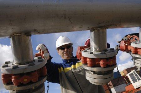Photo pour Ingénieur, travailleur, tournant de grandes pompes de pipeline, à l'intérieur de la raffinerie de pétrole et de gaz - image libre de droit