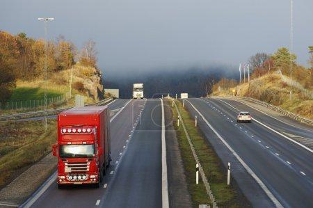 Photo pour Camions et voitures traversant un col brumeux. autoroute entourée d'arbres et de forêt - image libre de droit