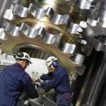 Engineers, steel workers with giant gear-wheel mac...