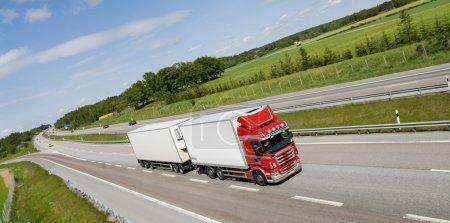 Photo pour Camion rouge et blanc conduisant sur route panoramique, vue surélevée et angle panoramique - image libre de droit