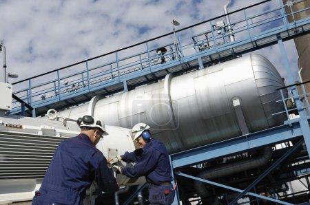 Photo pour Deux travailleurs du pétrole et des réservoirs géants de carburant et d'huile, travailleurs des machines - image libre de droit