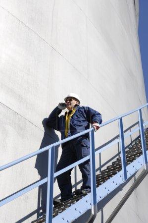 Photo pour Travailleur du pétrole et du gaz parlant au téléphone, debout sur les escaliers d'une grande tour de combustible - image libre de droit