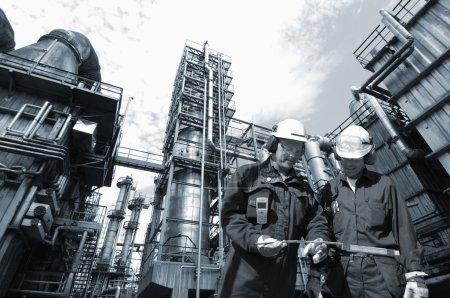 Photo pour Deux travailleurs chimiques avec une grande industrie pétrolière et gazière en arrière-plan, idée de tonification duplex bleu - image libre de droit